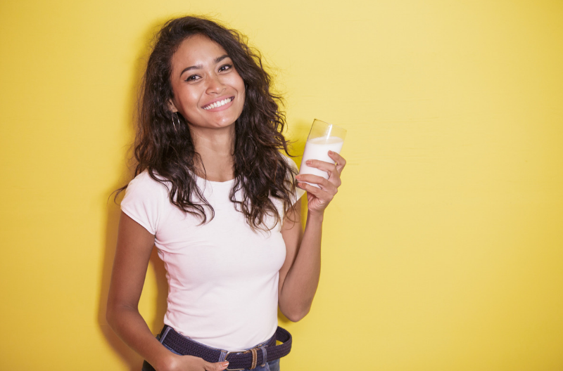 Smiling woman holding up a glass of milk against a yellow backdrop