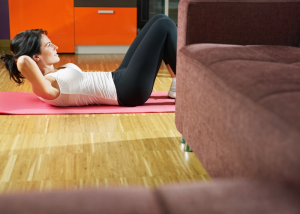 woman doing crunches in her living room