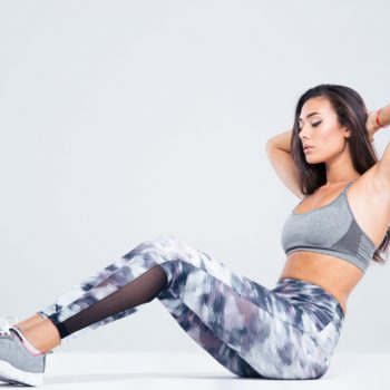 Woman in stylish exercise pants doing crunches