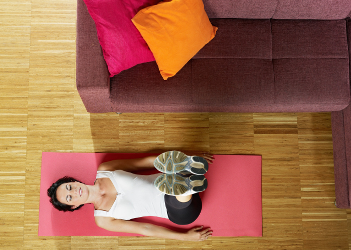 woman doing leg raise and hold ab exercises at home next to her couch