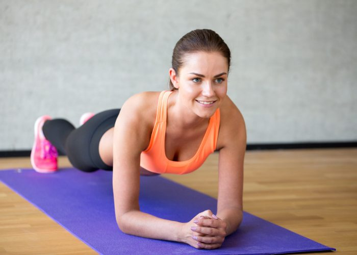 woman doing plank ab exercises at home on a yoga mat