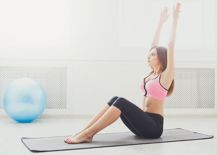 woman doing roll up stomach exercises at home
