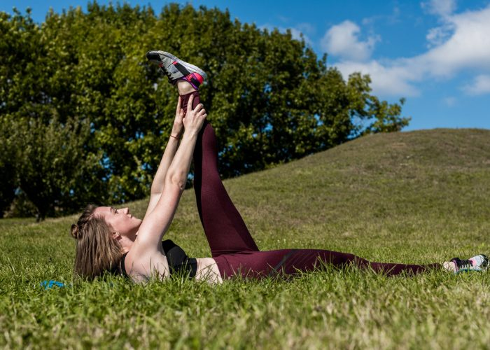 young woman doing scissor switches outdoors in a green field