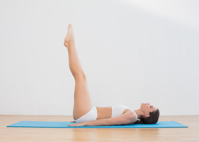 woman in white fitness gear doing toe touches