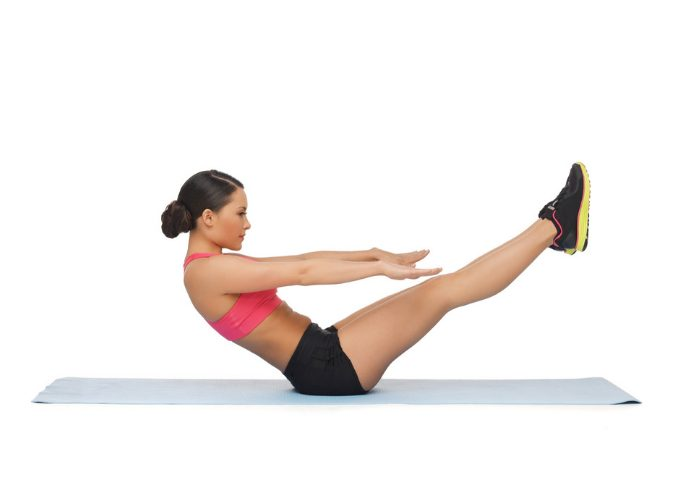 woman doing v crunch stomach exercises on a yoga mat