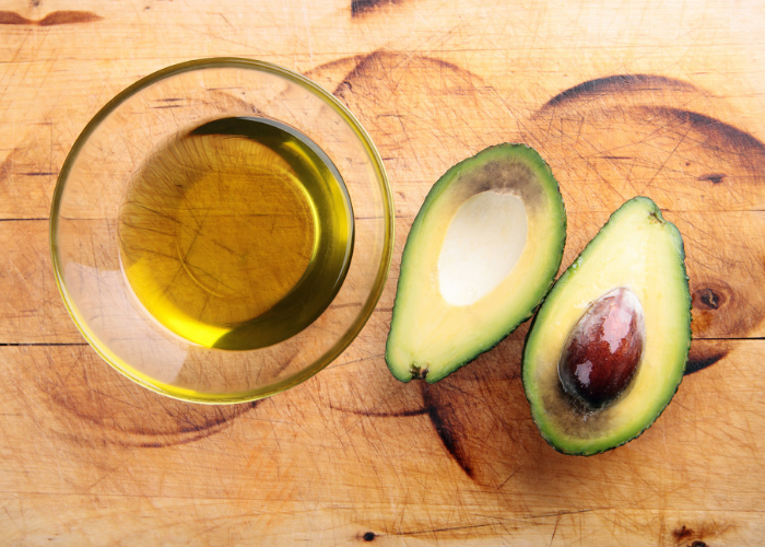 a small clear dish of avocado oil and two halves of a whole avocado beside it