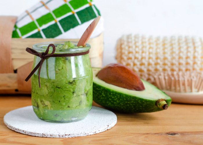 a fresh jar of DIY homemade avocado face mask, with wooden spa brush and towels behind