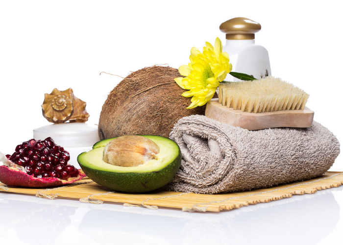 spa ingredients and essentials including avocado oil, coconut, towel, and brush on a table
