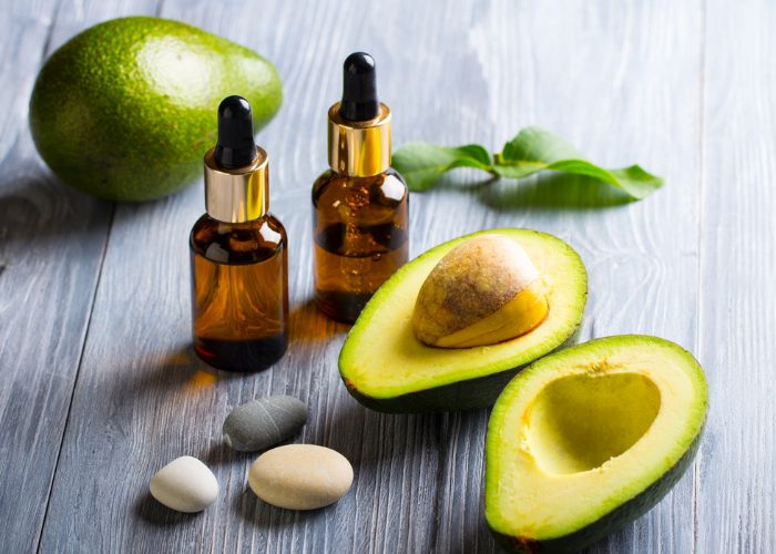 avocado oil in dark vials and fresh avocado being used to improve skin and hair condition