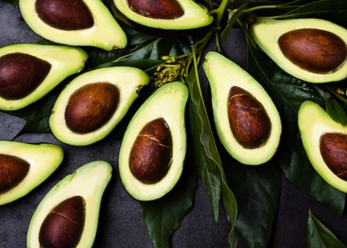 top down shot of a table filled with avocado halves with seeds