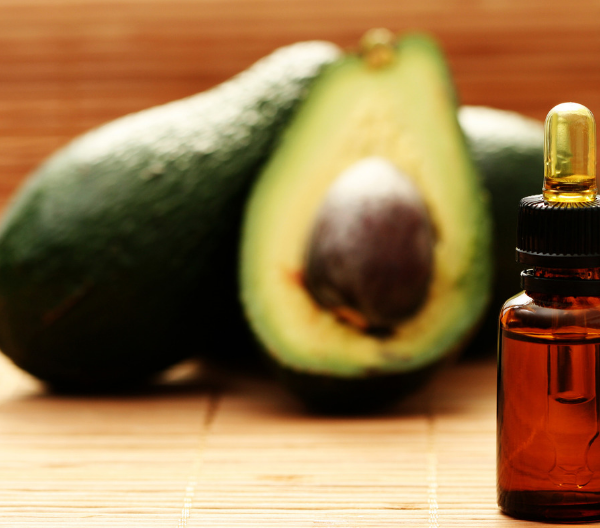 a small dark dropper vial of avocado oil with whole avocados behind it