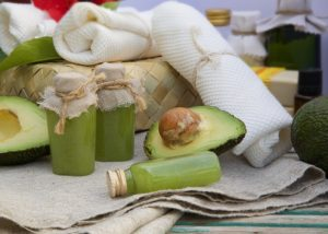 avocado oil and fresh avocados surrounded by other spa essentials