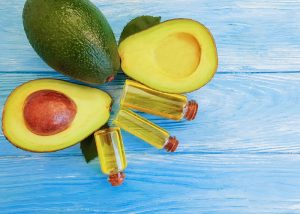 three vials of avocado oil, two halves of an avocado, and a whole avocado on a blue wooden table
