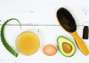 A composition of ingredients needed for healthy hair: fresh aloe vera, avocado oil, an egg, and a hair brush on a white table