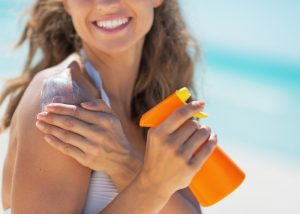 woman at the beach spraying on sunscreen and applying it on her shoulder and arms