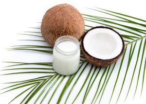 a jar of coconut oil, half a coconut, and a whole fresh coconut laid on a green palm leaf
