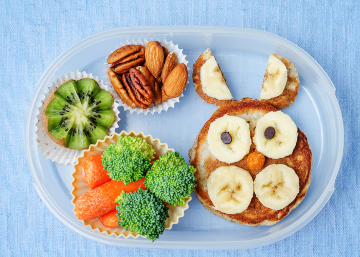 bento lunch box with broccoli, carrots, kiwi, almonds and banana pancake, organized using silicone cups