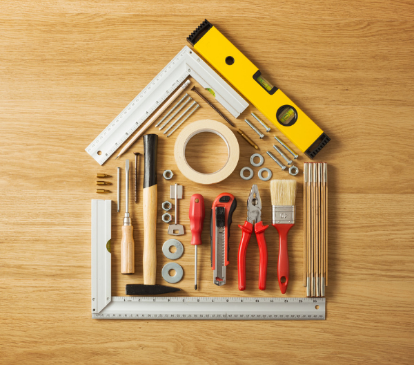 diy tools such as paint brushes, screwdrivers, rulers etc arranged in the shape of a house