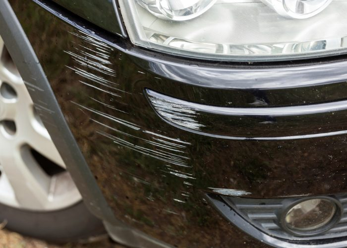 black car with white scratch marks on its fender