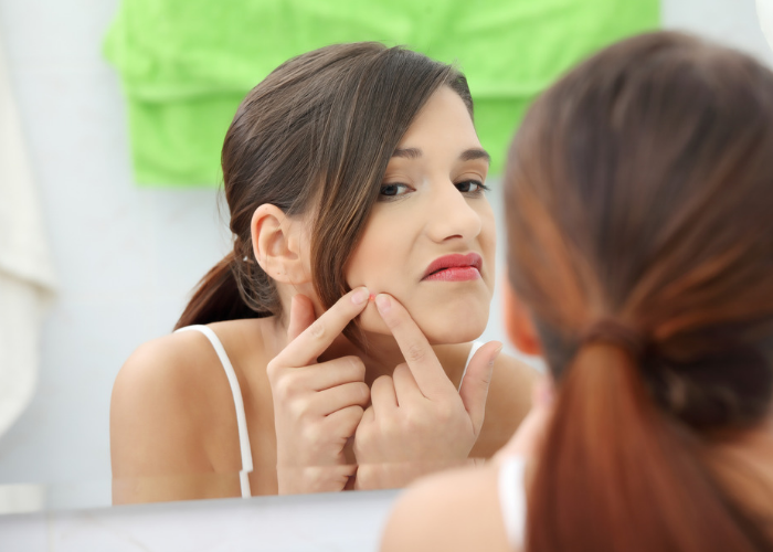 woman squeezing her zit in front of a mirror