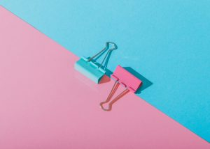 a flat lay of a blue and pink paper clip set on contrasting table backgrounds