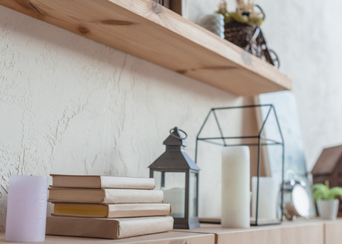 a DIY wall shelf with candles and books on it