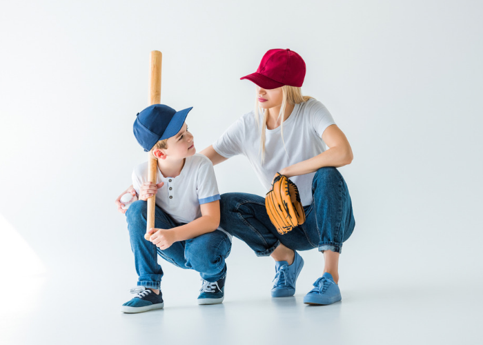 a mother and her son with blue and red baseball caps on holding a baseball bat and glove