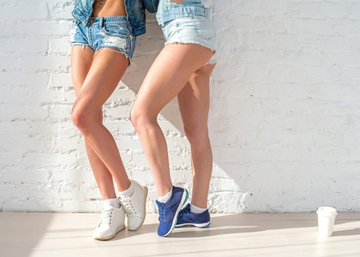 two girls wearing denim shorts with sneakers