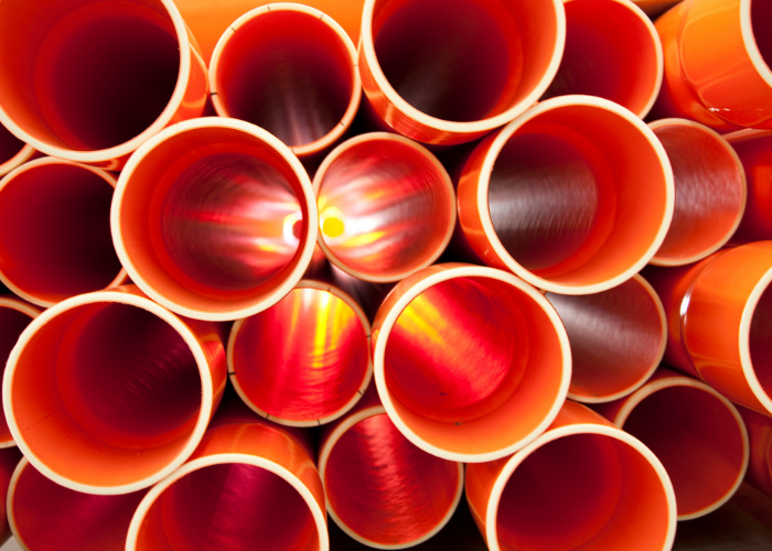 looking down the tube of orange pvc pipes