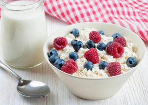 A breakfast bowl of cottage cheese topped with blueberries and raspberries