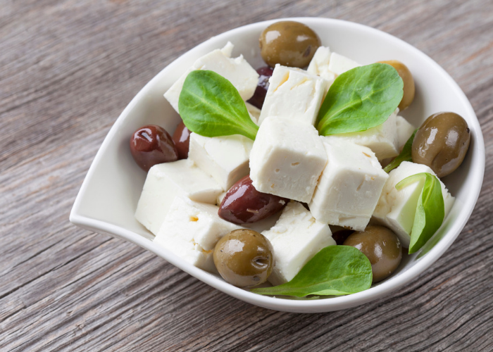 Cubes of feta cheese and olives in a small bowl