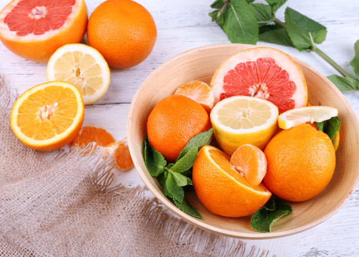a bowl of citrus fruits like grapefruit, oranges, and lemons in a wooden bowl
