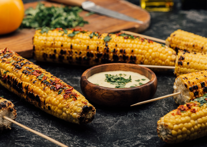 grilled corn on the cobs seasoned with paprika and parsley, served on black slate plates