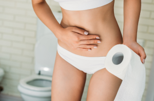 Woman with a food intolerance having a belly ache and holding a roll of toilet paper