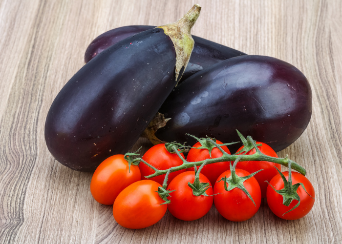 nightshade vegetables like eggplants and tomatoes on a wooden table