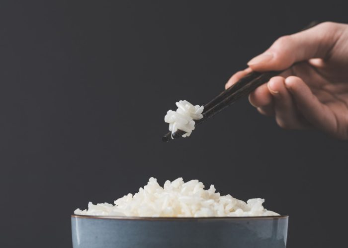 woman picking up a small bunch of glutinous rice with chopsticks over a bowl of rice