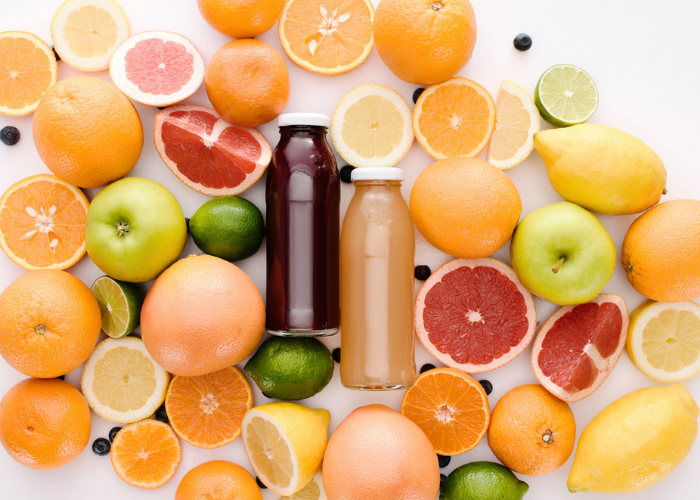 top down view of two bottles of juice laid down on a table, surrounded by sliced and whole citrus fruits