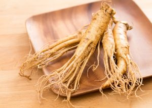 four small ginseng roots on a wooden plate