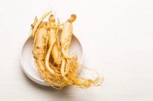 Top down shot of ginseng roots on a white dish