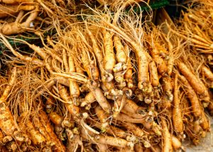 a pile of fresh ginseng roots in a market