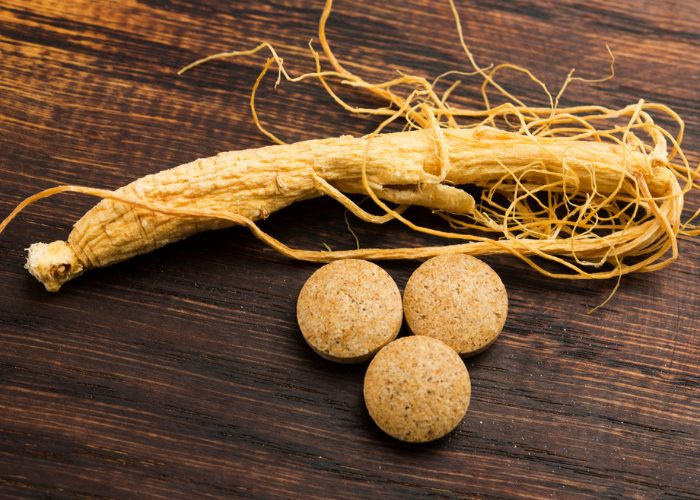 one ginseng root and three ginseng supplement capsules on a wooden table