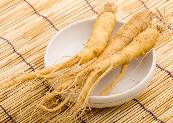 3 whole ginseng roots on a white dish on a bamboo mat