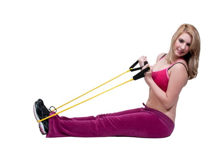 woman using a resistance band on her feet as part of an ankle sprain injury workout