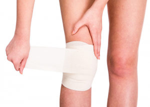 woman wrapping a bandage around her injured knee