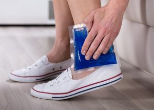 "woman holding an ice pack to her ankle injury, as part of the ""ice"" component of the RICE injury recovery procedure"