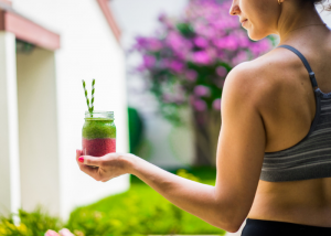 woman in sports bra holding a healthy red and green smoothie
