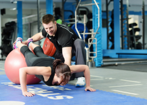 a woman working out with the help of a personal gym trainer
