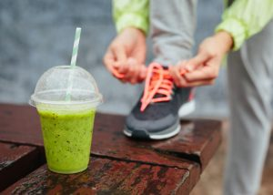 a cup of green smoothie on a wooden table with a woman tying her sports shoe shoelace in the background