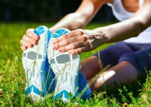 woman in running shoes stretching before running, which is a type of injury prevention exercise
