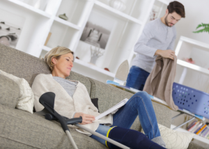 woman with leg in cast resting on a sofa with a carer doing chores
